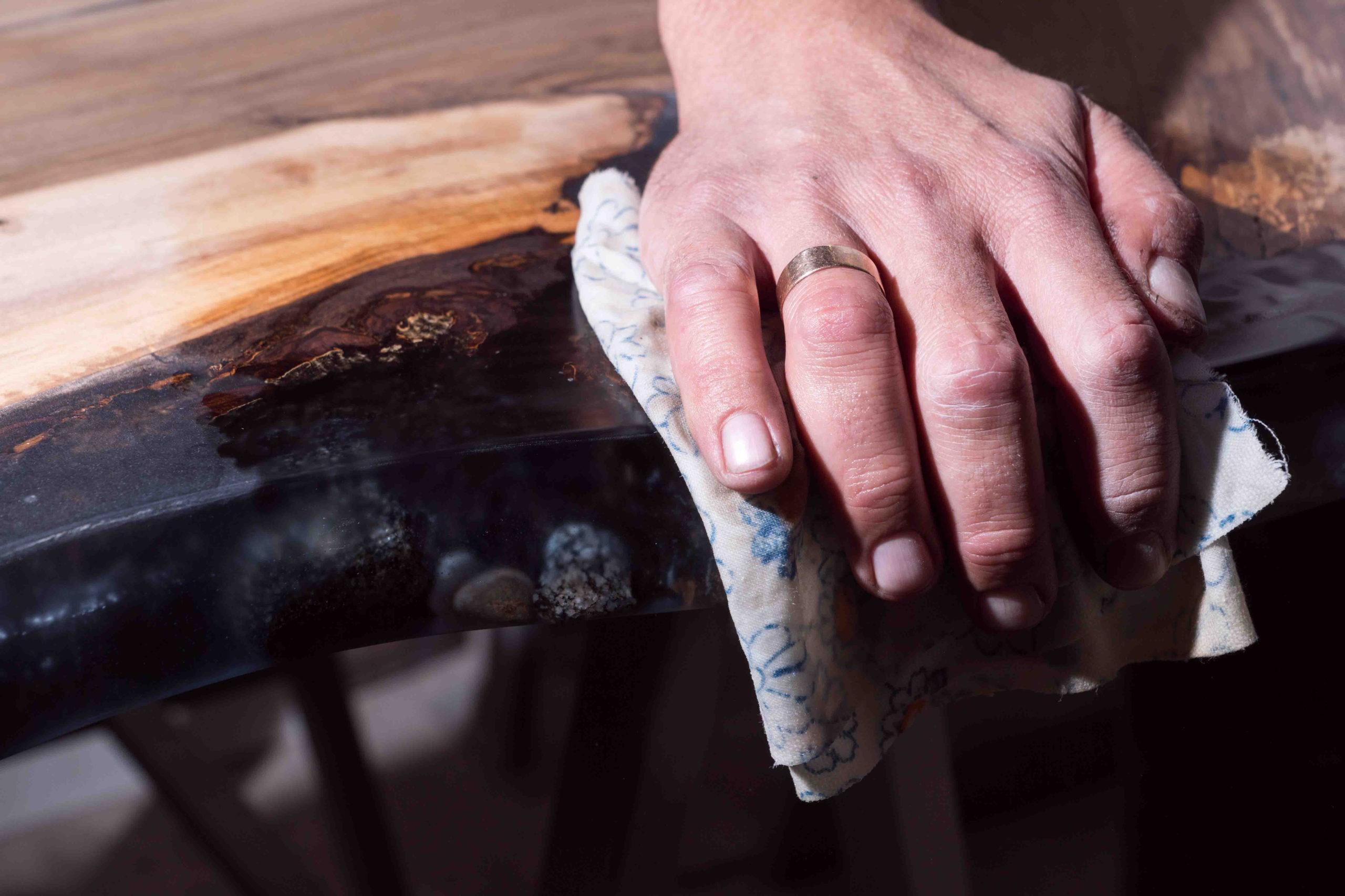 Ein Epoxidharztisch wird veredelt und per Hand poliert
